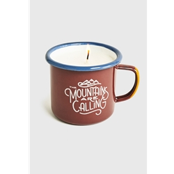 "United By Blue Mountains Are Calling Enamel Candle Mug är en emaljmugg med citatet ""The Mountains Are Calling and I Must Go"" och ett ljus i."